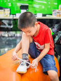 Young boy tying shoelace. Try Stock Image