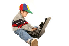 Young boy types on laptop. Isolated on white Royalty Free Stock Photo