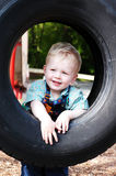 Young boy in tyre Royalty Free Stock Images