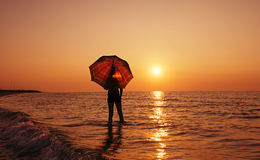 Young boy with umbrella on the beach at sunrise Stock Images