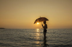 Young boy with umbrella on the beach at sunrise Stock Photos