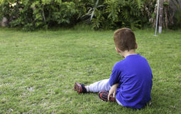 Young boy unhappy depressed. A young boy sits outside looking sad and depressed Royalty Free Stock Image