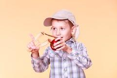 Young boy use sling shot shoot apple. Stock Photos