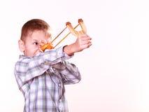 Young boy use sling shot shoot mandarine. Stock Photos