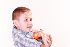 Young boy use sling shot shoot mandarine. Royalty Free Stock Photos