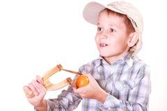 Young boy use sling shot shoot mandarine. Stock Photo