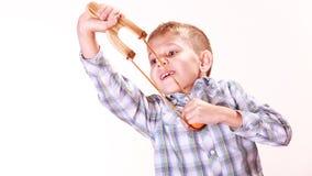 Young boy use sling shot shoot mandarine. Royalty Free Stock Images