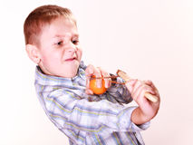 Young boy use sling shot shoot mandarine. Royalty Free Stock Images
