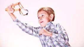 Young boy use sling shot shoot mandarine. Stock Images