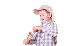Young boy use sling shot shoot mandarine. Stock Photography