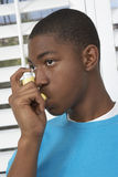 Young Boy Using Asthma Inhaler. Young African American boy using asthma inhaler royalty free stock photos