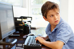 Young boy using computer at home Stock Images