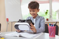 Young boy using 3d virtual reality headset at school. Science, futuristic technology concept. Excited young boy examining 3d vr glasss before trying virtual royalty free stock photos