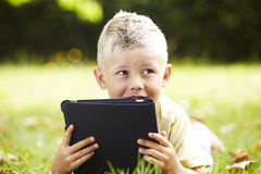 Young boy using digital tablet outdoors Royalty Free Stock Image
