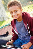 Young Boy Using Digital Tablet Sitting In Park Stock Image