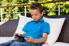 Young boy using his tablet Stock Images