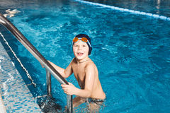 Young boy using ladder to exit swimming pool Stock Photo