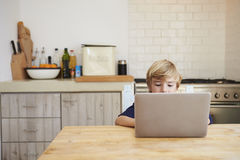 Young boy using laptop computer at kitchen table Stock Image