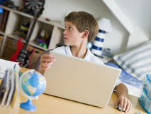 Young Boy Using A Laptop In His Bedroom Stock Images