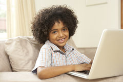 Young Boy Using Laptop At Home Stock Image