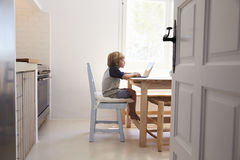 Young boy using laptop in kitchen, side view, from doorway Stock Photography