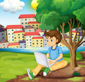 A young boy using the laptop under the tree at the riverbank Stock Photo