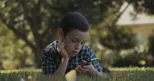 Young boy using a mobile phone outdoors on the grass