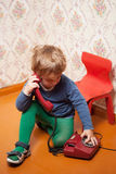 Young boy using red phone Stock Images