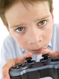 Young boy using videogame controller. And concentrating Royalty Free Stock Photography