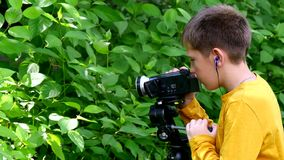 Young boy with video camera shoots film about nature of green park background. stock footage