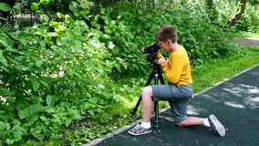 Young boy with video camera shoots film about nature of green park background. stock video footage