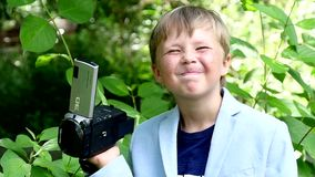 Young boy with video camera shoots film in nature of green park slow motion. Children outdoors in summer are creative work of cinema. Beautiful footage stock video footage