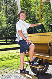 Young Boy on Wagon. A young boy posing on the back of a horse wagon before getting in stock photography