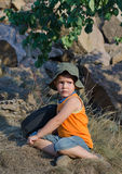 Young boy waiting alongside his rucksack Royalty Free Stock Photography