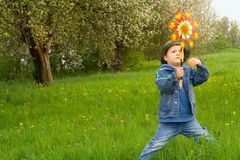 Young boy waits for the wind. Young boy waiting for the wind standing in the grass in springtime royalty free stock image