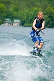 Young Boy on Wakeboard. Young boy having fun on his new wakeboard Royalty Free Stock Photo