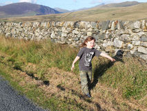Young boy walking alone in a remote location. A young boy walking beside a dry stone wall in Wales. Hills and mountains in the background. The boy is walking Royalty Free Stock Photo