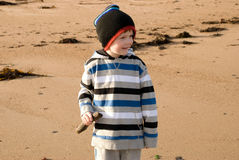 Young boy walking along the beach Stock Photo