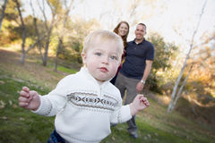 Young Boy Walking as Parents Look On From Behind Royalty Free Stock Photos