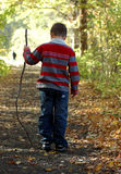 Young Boy Walking with Stick. Young boy on a wooded path.  He is holding a stick.  It is autumn Stock Photo