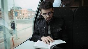 A young boy walking on a train, reading a book. Boy with glasses. 4k. A young boy walking on a train, at a table reading a book. Boy with glasses. 4k stock footage