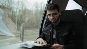 A young boy walking on a train, at a table reading a book. Boy with glasses. 4k. A young boy walking on a train, at a table reading a book. Boy with glasses stock footage