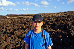 Young boy walking through volcanic area Stock Image