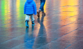 Young boy walking on wet pavement Royalty Free Stock Photography