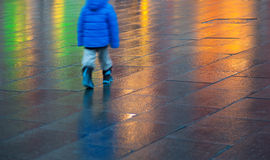 Young boy walking on wet pavement Stock Photo