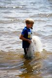 A young boy walks along the waterfront with a cast-net in his mouth ready to throw. A young boy walks along the water front with a cast net ready to throw stock photography