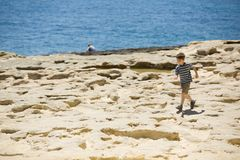 Young boy walks at the rocky beach, next to the blue sea, in striped shirt. Royalty Free Stock Photo