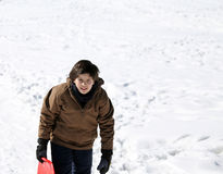 Young boy walks with tobogganing  on fresh snow in the winter Stock Photos