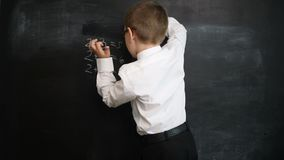 Young boy washing blackboard after solving maths expressions. Creative concept of back to school and study. Pre school stock video footage