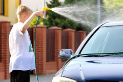 Young boy washing the car with hose Royalty Free Stock Image
